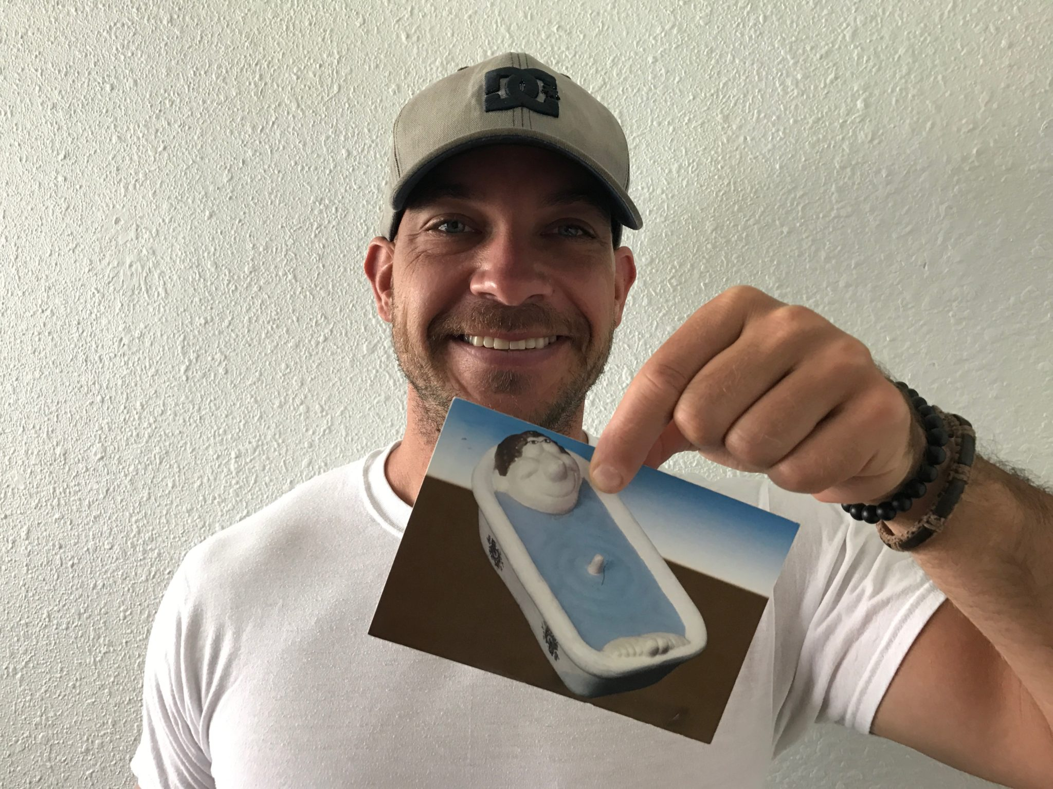 man wearing baseball hat smiling while holding a postcard with image of a man in a bathtub