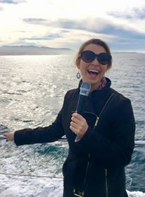 woman laughing while speaking into a microphone on a boat