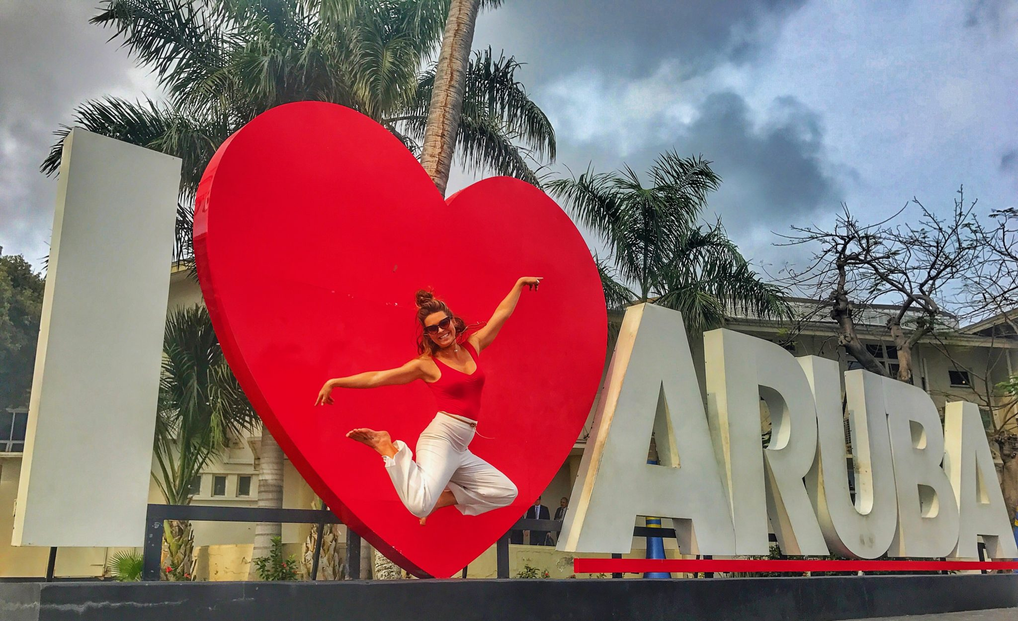 woman jumping at the I heart Aruba sign
