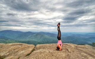 head stand mountain woman