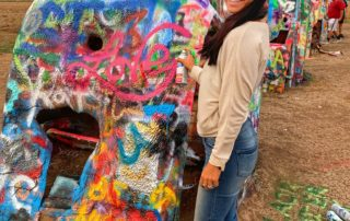 woman smiling at Cadillac Ranch